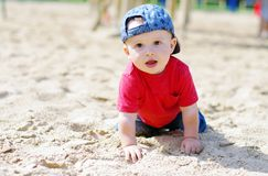 Baby boy creeps on playground Royalty Free Stock Photo