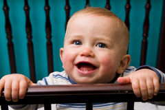 Baby boy in crib. Happy and laughing baby boy in crib Royalty Free Stock Photos