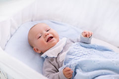 Baby boy in a crib under knitted blanket Royalty Free Stock Photos