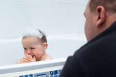 Baby boy crying in bath Stock Images