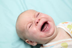 Baby boy crying. On the bed at home Stock Images