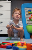 A baby boy crying in children room Stock Images
