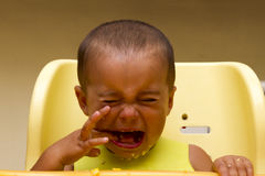 Baby boy crying while eating stock image