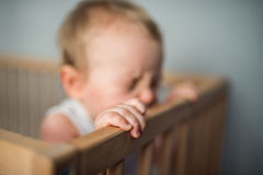 Baby boy crying in his crib. Cute blond baby boy with blue eyes staying in his crib, the child is happy and holds the crib`s edges Royalty Free Stock Image