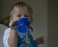 Baby boy with cup at messy mealtime Stock Images