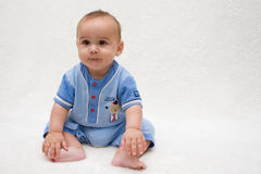 Baby boy with cute grin. A six month old baby boy can barely sit up and has a cute grin for the camera. He is wearing a light blue and red romper. He is royalty free stock images