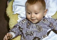 Baby boy. Cute smiling baby boy lying on a lambskin Stock Photo