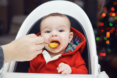 Baby boy with dark black eyes sitting in high chair in kitchen looking in camera eating meal puree Royalty Free Stock Photos