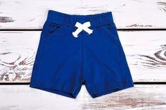 Baby boy dark blue cotton shorts. Childrens summer shorts on white wooden background. Brand kids apparel on sale Stock Photos