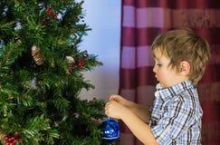 Baby boy decorates Christmas tree Stock Photography
