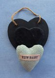 Baby boy decoration. A new baby small pillow with a black slate heart shape on a blue background Stock Image