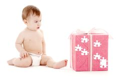 Baby boy in diaper with big puzzle gift box. Picture of baby boy in diaper with big puzzle gift box Royalty Free Stock Photos