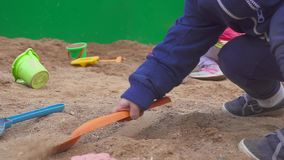 Baby boy digging in the sandbox. Smiles and touches the sand. Baby boy digging in the sandbox. Smiles and touches the sand stock video footage