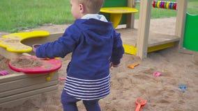 Kids Games. Baby boy digging in the sandbox. Smiles and touches the sand. Baby boy digging in the sandbox. Smiles and touches the sand stock footage