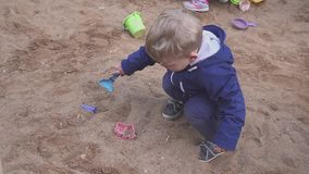 Kids Games. Baby boy digging in the sandbox. Smiles and touches the sand. Baby boy digging in the sandbox. Smiles and touches the sand stock video footage