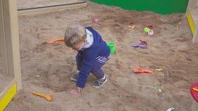 Kids Games. Baby boy digging in the sandbox. Smiles and touches the sand. Baby boy digging in the sandbox. Smiles and touches the sand stock video