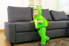 Baby boy with dinosaur halloween party costume. At home stock photography