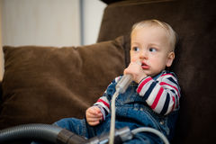 Baby boy doing a mucus suction by himself Royalty Free Stock Photos