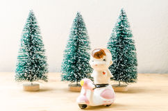 Baby boy doll and motorbike with chrismas trees background Stock Photos