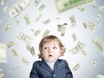 Baby boy and dollar bills falling Stock Photos
