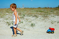 Baby boy dragging toy car walking at field Royalty Free Stock Photography