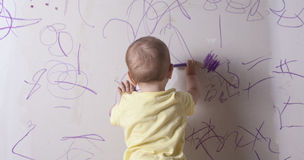 Baby boy drawing on plasterboard wall Stock Image