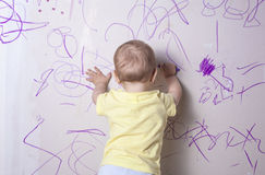 Baby boy drawing on plasterboard wall Royalty Free Stock Image