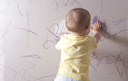 Baby boy drawing on plasterboard wall Stock Images