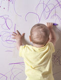Baby boy drawing on plasterboard wall Royalty Free Stock Photos