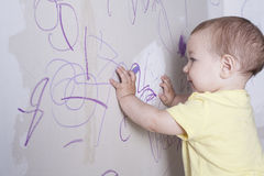 Baby boy drawing with wax crayon on plasterboard wall Stock Photography