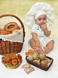 Baby boy dressed as a cook eats a biscuit. Baby boy dressed as a cook eating a biscuit sits on a light background with baskets of breads and rolls Royalty Free Stock Images