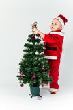 Baby boy dressed as Santa Claus decorating  Christmas tree, hang. Ing ornaments. White background Royalty Free Stock Image