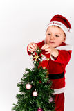 Baby boy dressed as Santa Claus putting the star on the top of C. Hristmas tree. Decorating. White background Stock Photography