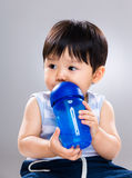 Baby boy drink with water bottle and look away Royalty Free Stock Images