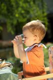 Baby boy drinking. Two years old baby boy drinking. Family BBQ party outdoor, in the garden stock photos