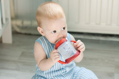 Baby boy drinking from baby cup Royalty Free Stock Photography
