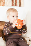 Baby boy drinking from a big jar Stock Images