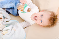 Baby boy drinking from bottle Stock Images