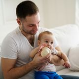 Baby boy drinking from bottle. father feeding son royalty free stock photography