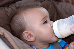 Baby boy drinking bottle in stroller Royalty Free Stock Photo