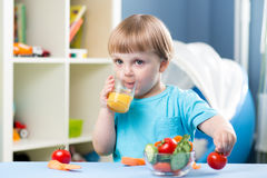 Baby boy drinking juice at table in children room Stock Images