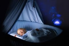 Baby boy drinking milk in bed. Adorable baby drinking milk in blue bassinet with canopy at night. Little boy in pajamas with formula bottle getting ready to Royalty Free Stock Photo
