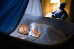 Baby boy drinking milk in bed Stock Photography