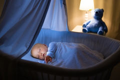 Baby boy drinking milk in bed Stock Images