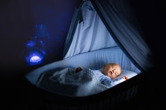 Baby boy drinking milk in bed. Adorable baby drinking milk in blue bassinet with canopy at night. Little boy in pajamas with formula bottle getting ready to Stock Images