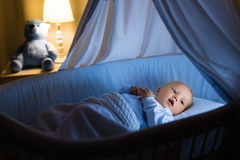 Baby boy drinking milk in bed. Adorable baby drinking milk in blue bassinet with canopy at night. Little boy in pajamas with formula bottle getting ready to Stock Photos