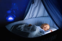 Baby boy drinking milk in bed. Adorable baby drinking milk in blue bassinet with canopy at night. Little boy in pajamas with formula bottle getting ready to Royalty Free Stock Images