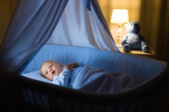 Baby boy drinking milk in bed. Adorable baby drinking milk in blue bassinet with canopy at night. Little boy in pajamas with formula bottle getting ready to Stock Photo