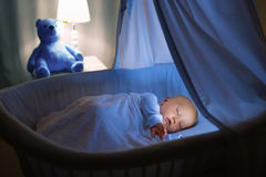Baby boy drinking milk in bed. Adorable baby drinking milk in blue bassinet with canopy at night. Little boy in pajamas with formula bottle getting ready to Stock Image