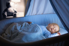Baby boy drinking milk in bed. Adorable baby drinking milk in blue bassinet with canopy at night. Little boy in pajamas with formula bottle getting ready to Stock Photography